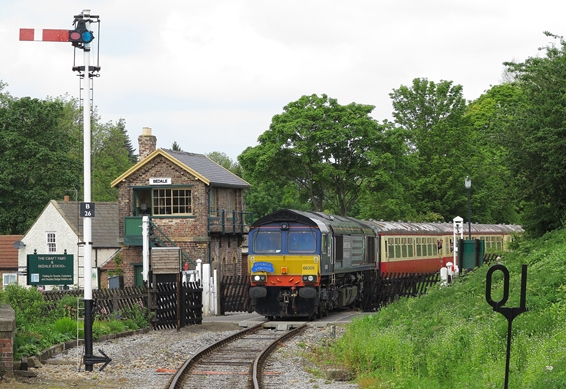 Diesel loco by the signal box approaching Bedale Station
